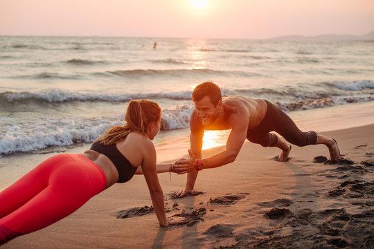 Couple Doing Pushups on Beach