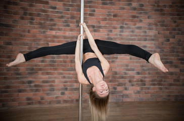 Blonde girl training pole dance in a studio
