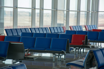 Empty seats in red-blue colors in the departure lounge at the airport