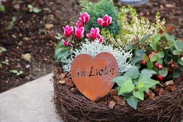 Einpflanzung auf dem Friedhof mit Blumen und Herz - In Liebe