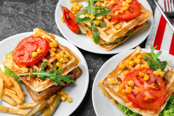 Delicious waffles with french fries and vegetables on plates