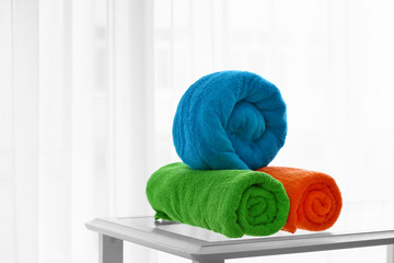 Rolled bright terry towels on table