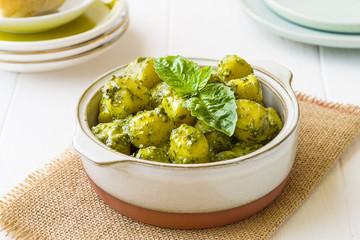Gnocchi with 'Pesto' sauce, in terracatta bowl, on white woodwn background.