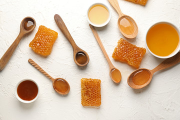 Composition with honey, spoons and honeycombs on white table