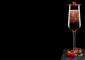 Elegant glass of pink rose champagne with raspberry on stick with fresh berries and mint leaf on black marble board on black background.Space for text