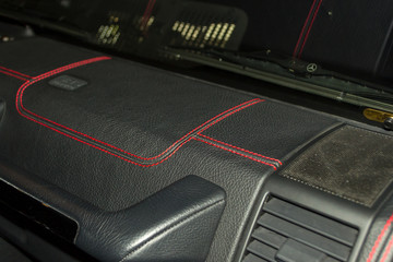 A view of a part of the interior of the car panel from leather of black color, stitched double thread of red color with contrast stitching in a vehicle interior design workshop