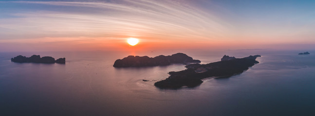 Aerial view of panoramic nature scene with colorful sunset sky and lonely islands in Indian ocean. Bright pink, blue, orange colors. Travel Background. Nature landscape