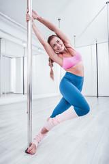 Obraz Beaming dancer. Beaming positive pole dancer wearing pink top feeling joyful while training all day - fototapety do salonu