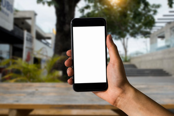 Mockup image of hand holding white mobile phone with blank white screen in garden.