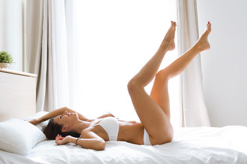 Beautiful smiling young woman with fresh skin in underwear having fun lying on bed at home.
