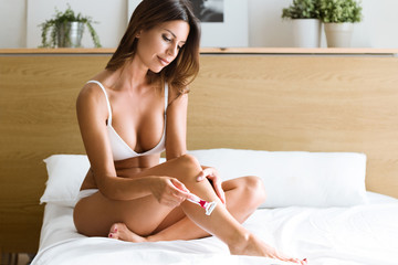Beautiful young woman shaving her attractive legs on the bed at home, Wall mural