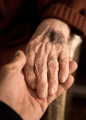 Adult son holding mothers senior hand at home