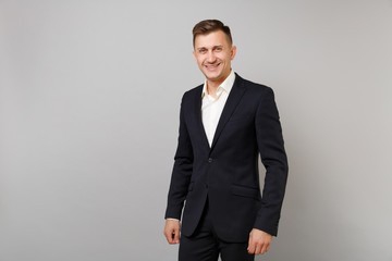 Portrait of handsome smiling young business man in classic black suit, white shirt standing isolated on grey wall background in studio. Achievement career wealth business concept. Mock up copy space.