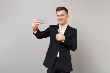 Joyful young business man in classic black suit showing thumb up, doing taking selfie shot on mobile phone isolated on grey background. Achievement career wealth business concept. Mock up copy space.