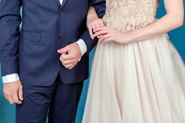 Hands of bride and groom in a wedding dress suit and white dress hold gently, close-up