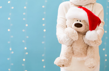 Woman holding a teddy bear with Santa hat on a shiny light blue background