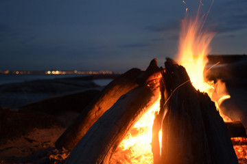 Wooden logs stacked in a fire, burning in the sand. The picture was taken on a summer evening.