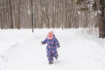 Family, children and nature concept - Beautiful little child girl have fun in winter park