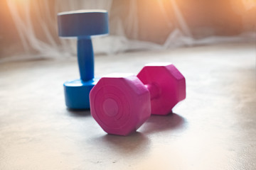 The blurru light design background of dumbbell put on ground floor,the accessory for weight lifting and built muscle