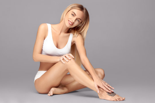 Perfect slim toned young body of the girl or fit woman at studio. The fitness, diet, sports, plastic surgery and aesthetic cosmetology concept.