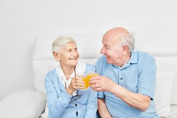 Wall Mural - Glückliches Senioren Paar stößt an mit Orangensaft