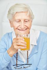 Wall Mural - Lächelnde Seniorin trinkt ein Glas Orangensaft