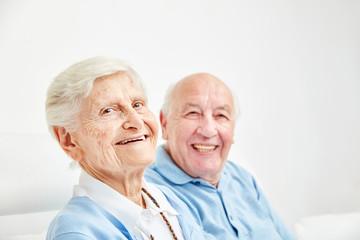 Glückliches Rentner Paar sitzt auf dem Sofa