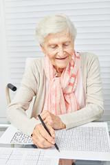 Wall Mural - Seniorin macht Sudoku als Gedächtnistraining
