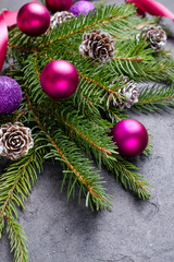 Christmas stone background with branch of a fir tree, pine cones and decorations