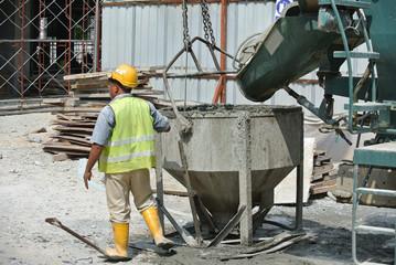 Concrete mixer lorry pouring wet concrete into concrete bucket at the construction site.