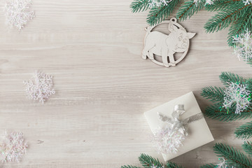 Christmas composition. Christmas gift, wooden snowflakes and figurines, pine cones, fir branches on wooden white ba