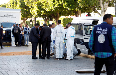 Police secure the area as forensic experts work near the site of an explosion in the center of the Tunisian capital Tunis