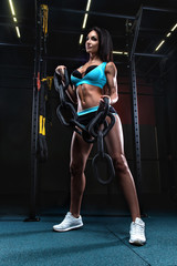 Sexy fitness brunette woman is doing biceps curls with chain in the gym