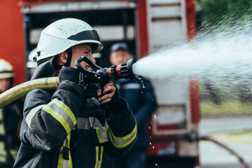 selective focus of firefighter with water hose extinguishing fire on street
