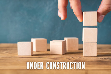 "hand is stacking blank cubes and the message ""under construction"""