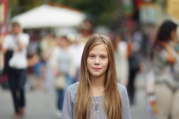 Portrait of a teenage girl on a background of people in a big city. A teenage girl in a crowd of people.