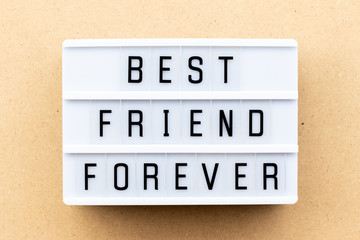 Light box with word best friend forever on wood background
