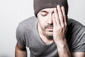 portrait homme masculin bonnet jeune casual souffrance mal malade moral psychologie souffrir problème main bras visage caché réfléchir besoin calme serein maux de tête gris quarantaine 40 ans personne