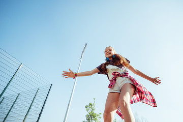 Be careful. Amazing longhaired girl raising her arms while enjoying active way of life