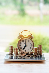 Alarm clock with stacks of coins on nature background