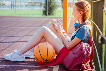 Catch the moment. Cheerful girl sitting in semi position while staring at screen of her gadget