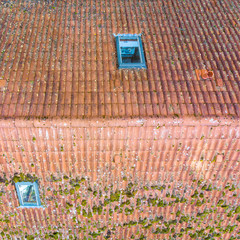 Inspection of the red tiled roof of a single-family house, inspection of the condition of the tiles on the roof of a detached house