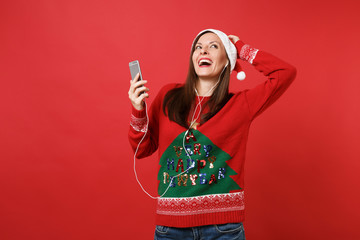 Funny young Santa girl with earphones looking up, put hand on head hold mobile phone listen music isolated on red background. Happy New Year 2019 celebration holiday party concept. Mock up copy space.