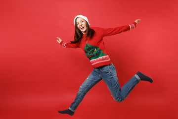 Laughing young Santa girl in knitted sweater, Christmas hat jumping, spreading hands, legs isolated on bright red background. Happy New Year 2019 celebration holiday party concept. Mock up copy space.