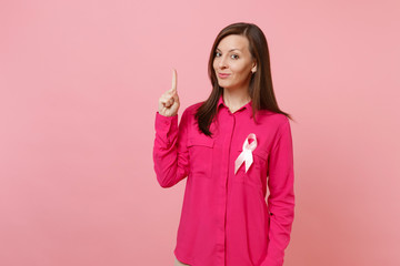 Woman in rose clothes with pink silk ribbon symbol isolated on pastel wall background, studio portrait. Medical healthcare gynecological oncology, Breast Cancer Awareness concept. Mock up copy space.