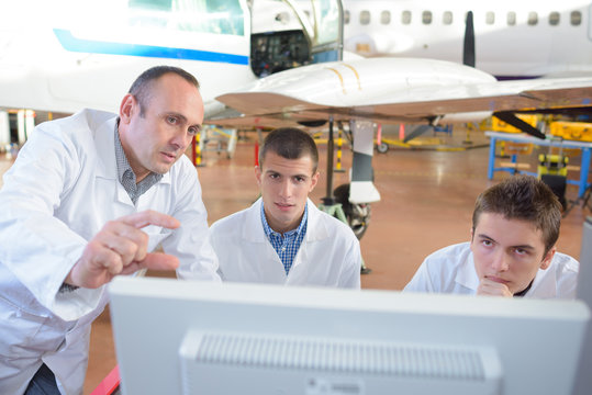 team of aircraft engineers repairing parts of jet