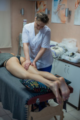 A professional masseuse does an anti-cellulite massage of the client's buttocks. Massage the hips. Masseur doing anti-cellulite hand massage on the back of the thigh in the spa
