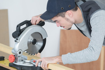 carpenter are cutting wooden with circular saw