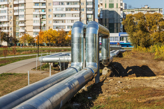 Modern Elevated Heat Pipes. Pipeline above ground, conducting heat to heat city. Urban heat line in metal insulation in residential quarter of city. Open laying on pillars. Municipal heat supply