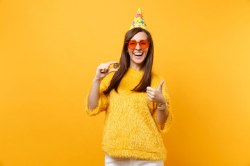 Laughing young woman in orange heart glasses, birthday hat showing thumb up holding bitcoin metal coin of golden color future currency isolated on yellow background. People sincere emotions lifestyle.